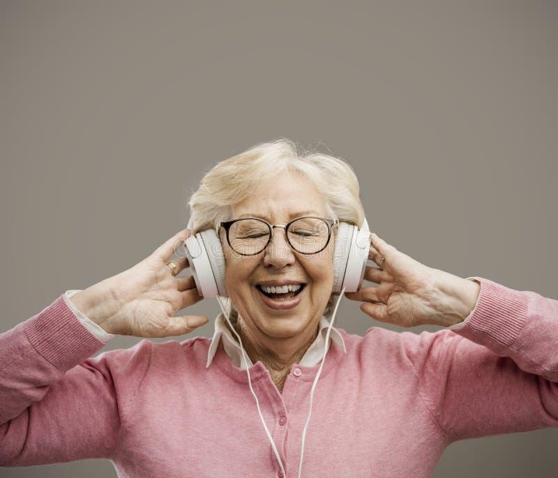 愉快的资深妇女佩带的耳机 库存图片