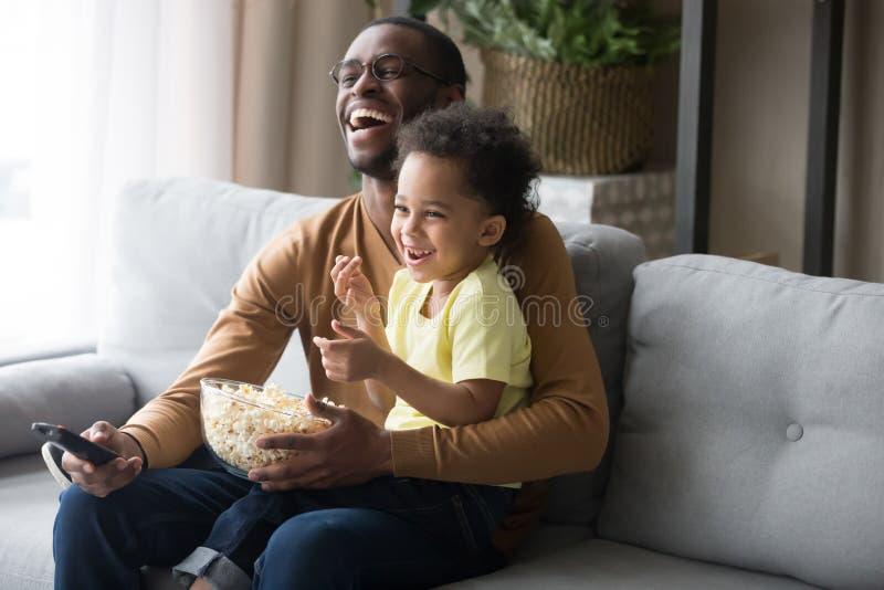 愉快的非洲爸爸和孩子儿子笑的观看的滑稽的喜剧 免版税库存照片