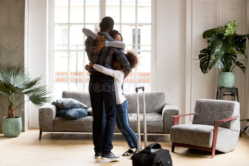 愉快的非裔美国人的家庭拥抱欢迎的爸爸家 库存照片