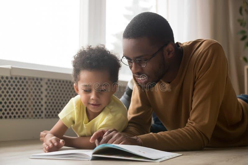 愉快的黑父亲和小孩儿子看书在家 免版税库存照片