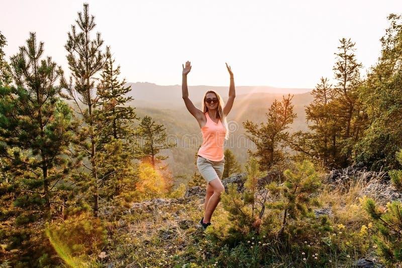 愉快的30岁的妇女身分在山顶部 免版税库存图片
