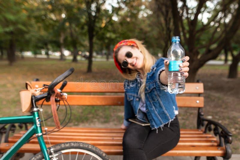 愉快,时髦的女孩坐一条长凳在公园在自行车附近和展示一个瓶在照相机的水 库存图片