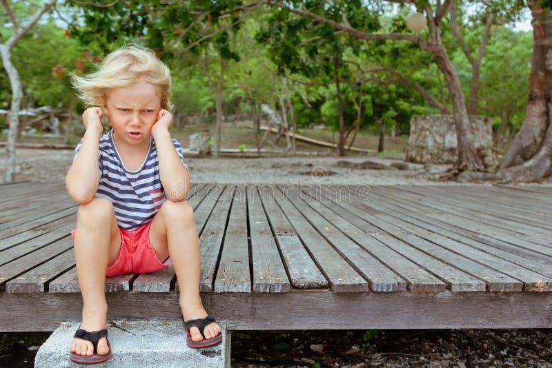 懊恼,不快乐的白种人孩子面孔画象与横渡的胳膊的 库存图片