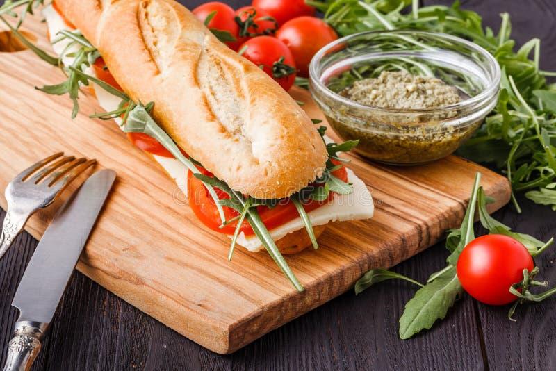 敬酒的panini用在切板的火腿、乳酪和芝麻菜三明治 免版税库存图片