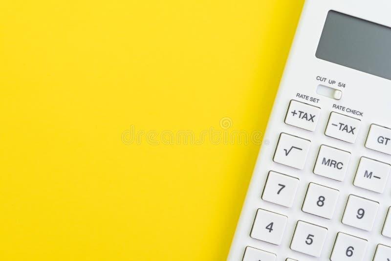 数学、税金计算、财务或者投资概念,在坚实黄色背景的白色干净的计算器与拷贝空间 免版税库存图片