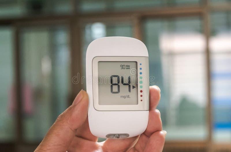 数字手扶的血糖探测器用途测量在医院和显示正常血糖八十四的耐心血糖 免版税图库摄影