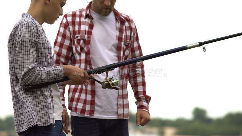教他的十几岁的儿子的父亲对鱼,熔铸了钓鱼竿和用途设备 免版税库存图片