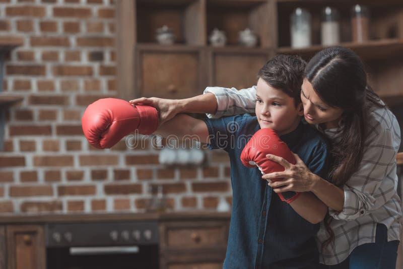 教她的拳击手套的年轻母亲小儿子如何装箱 免版税图库摄影