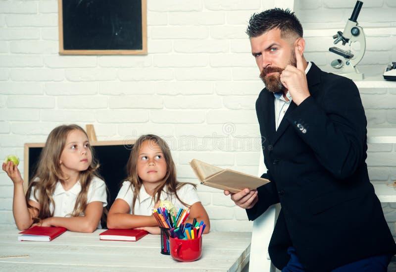 教育在知识天 上课时间姐妹和父亲在图书馆里 老师人读了故事给吃苹果的女孩 免版税库存照片
