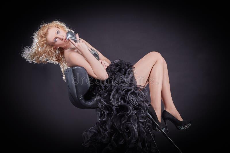 执行一个音乐作品的情感女歌手在一间录音室 免版税库存照片
