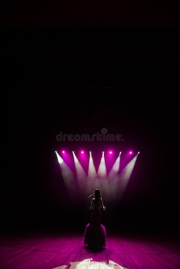 执行在阶段的长的褂子的女孩 唱歌在光前面的阶段的女孩 歌手身分剪影  库存图片