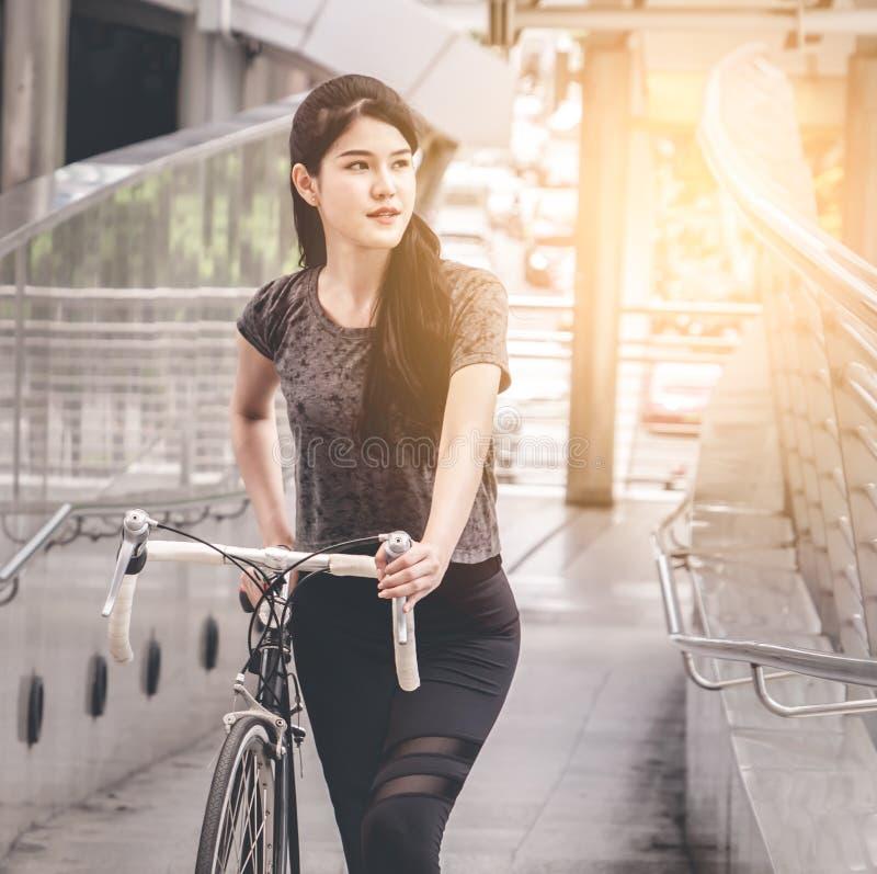 扯拽她的自行车的女孩对火车站 免版税库存图片