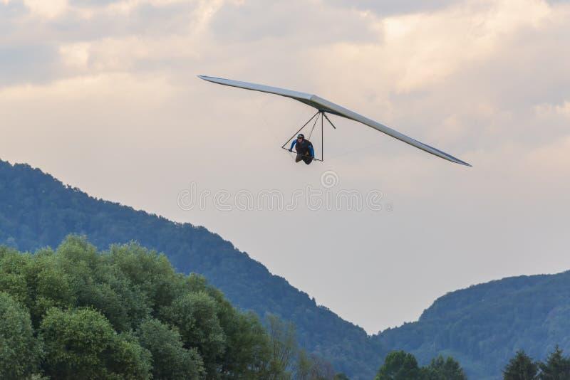 2018-06-30托尔明,斯洛文尼亚 悬挂式滑翔机飞行员接近着陆 免版税库存图片