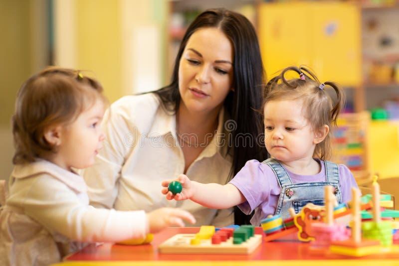 托儿所使用与日托中心游戏室的老师的婴孩小组 免版税库存照片