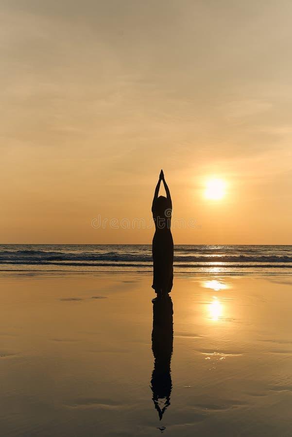 打扮在一件美丽的长的礼服和做瑜伽的妇女在海滩的日落 库存照片