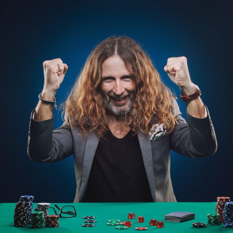 打扑克的长发帅哥在赌博娱乐场 免版税库存照片