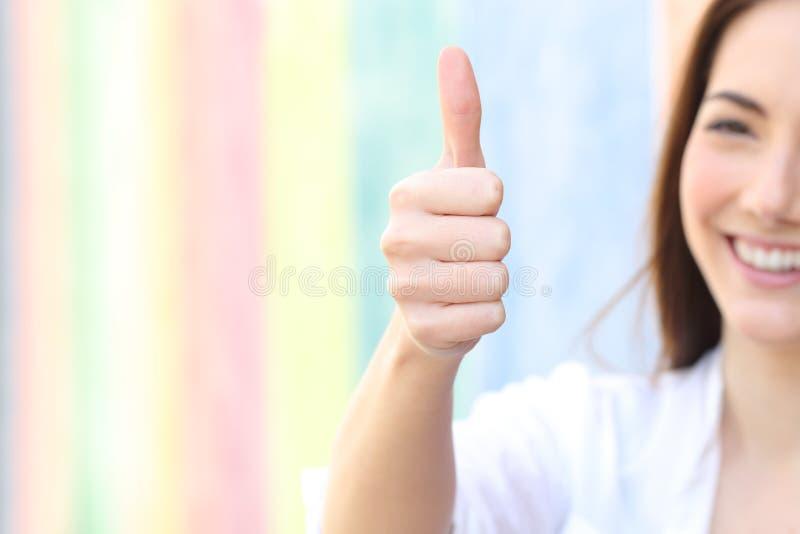 打手势在一条五颜六色的街道的愉快的妇女赞许 免版税库存照片