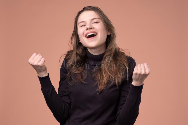 打手势和保持拳头的愉快的年轻女人 库存照片