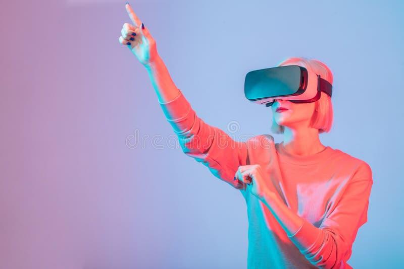 打手势的年轻女人,当戴VR眼镜时 免版税库存照片