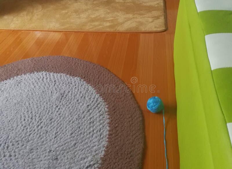 手工制造地毯,在地板上的编织的球在小屋子 库存照片