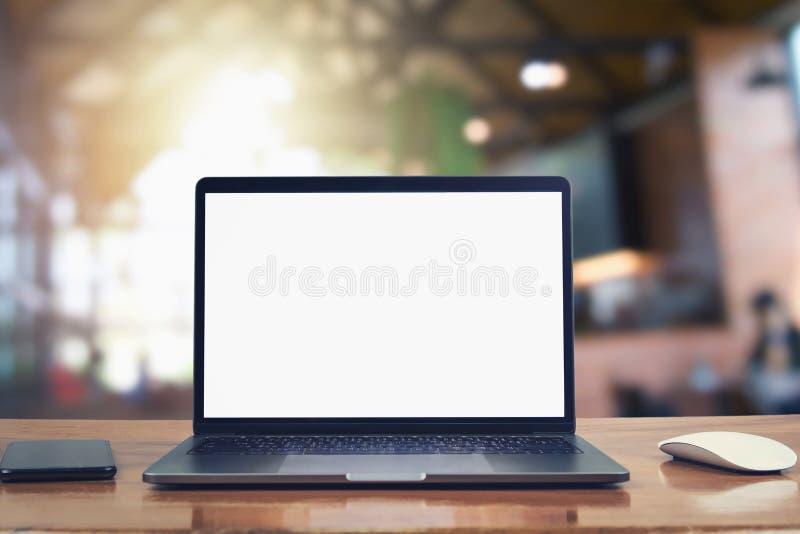 手提电脑空白白色屏幕和机动性在桌上在咖啡馆 图库摄影