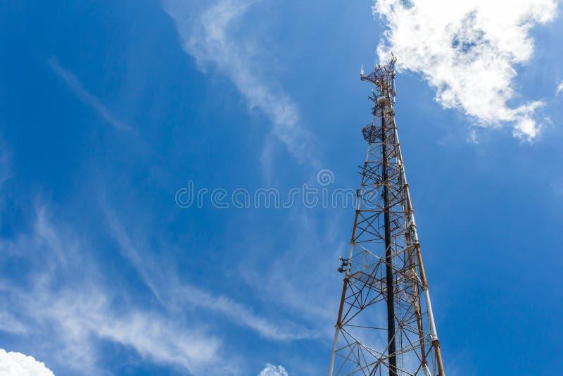 手机通信中继器天线塔,与天空蔚蓝和白色云彩 免版税库存图片