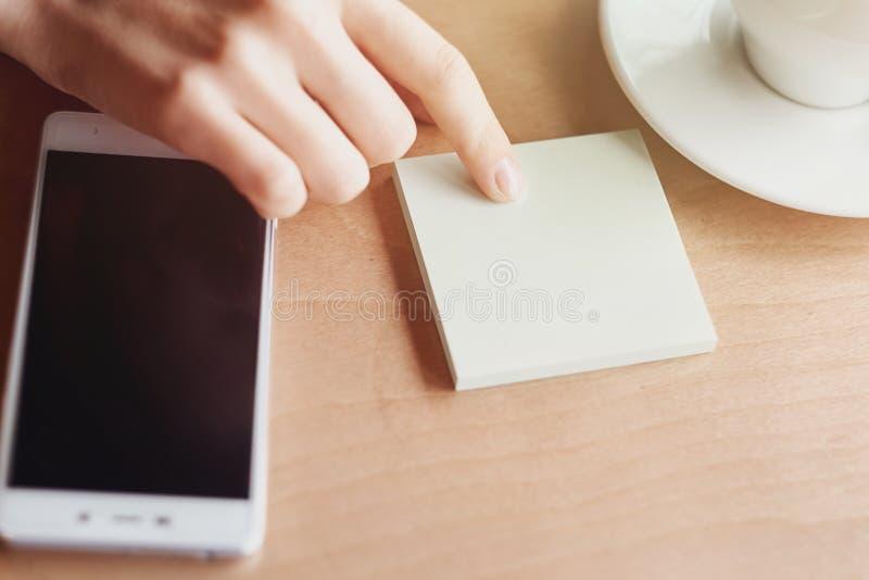 手指、贴纸和智能手机 计划的企业想法 空的背景地方的关闭文本的 免版税库存图片