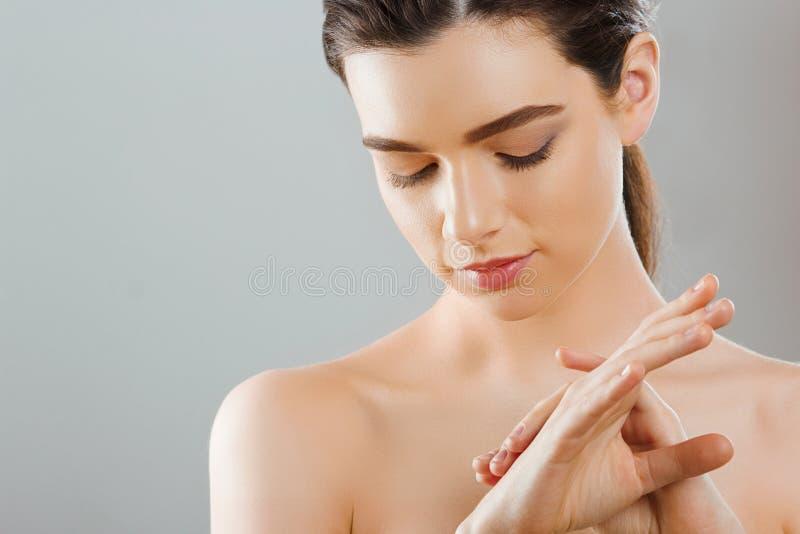 手护肤 关闭应用奶油,化妆水的女性手 有红色修指甲的美女手 免版税库存照片