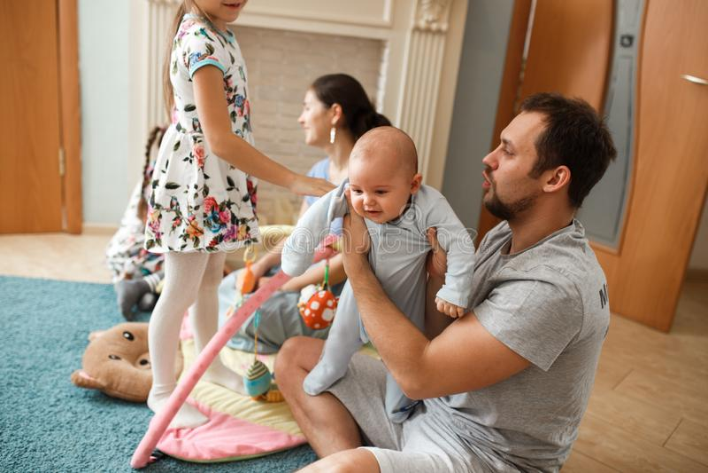 所有家庭父亲、母亲、花费时间的两个女儿和一点小儿子在地毯上在屋子里 库存照片