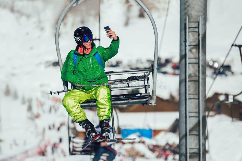 拍与聪明的手机照相机的滑雪者selfie照片坐滑雪电缆车 免版税库存图片