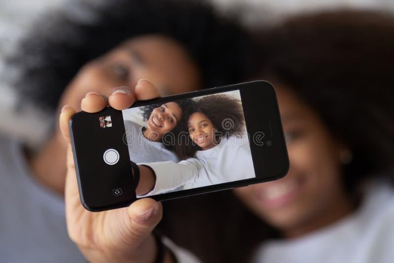 拍摄非洲母亲的女儿显示在智能手机的selfie照片 免版税库存照片