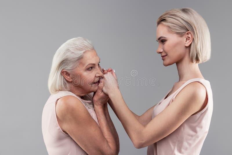 拥抱她放光的女儿的手的灰发的宜人的老母亲 库存照片