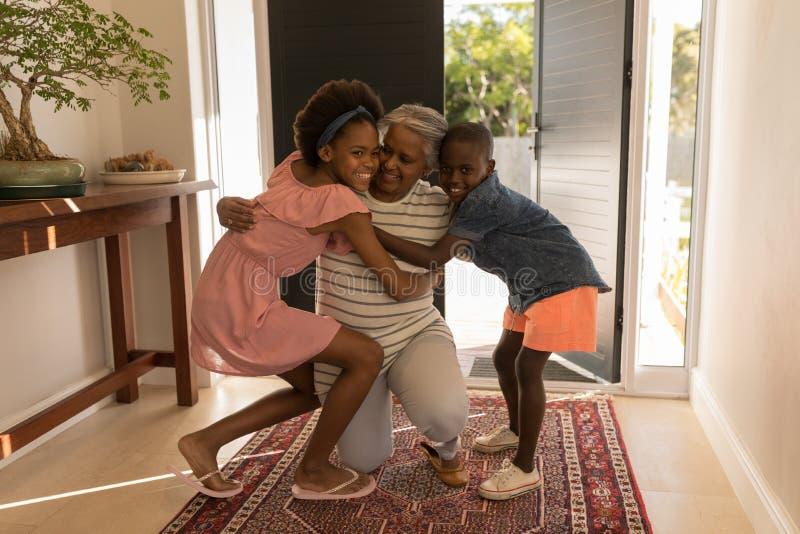 拥抱她的孙的祖母,当在家时坐她的膝盖 免版税库存图片