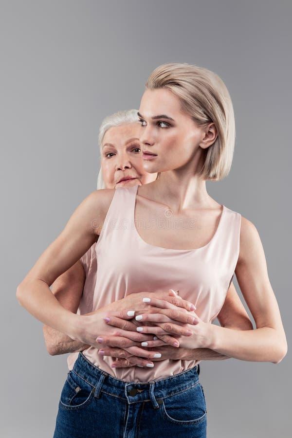 拥抱她的年轻女儿的防护灰发的老母亲 免版税库存图片