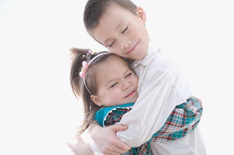 拥抱在白色背景隔绝的朋友 愉快的孩子mis 免版税库存照片