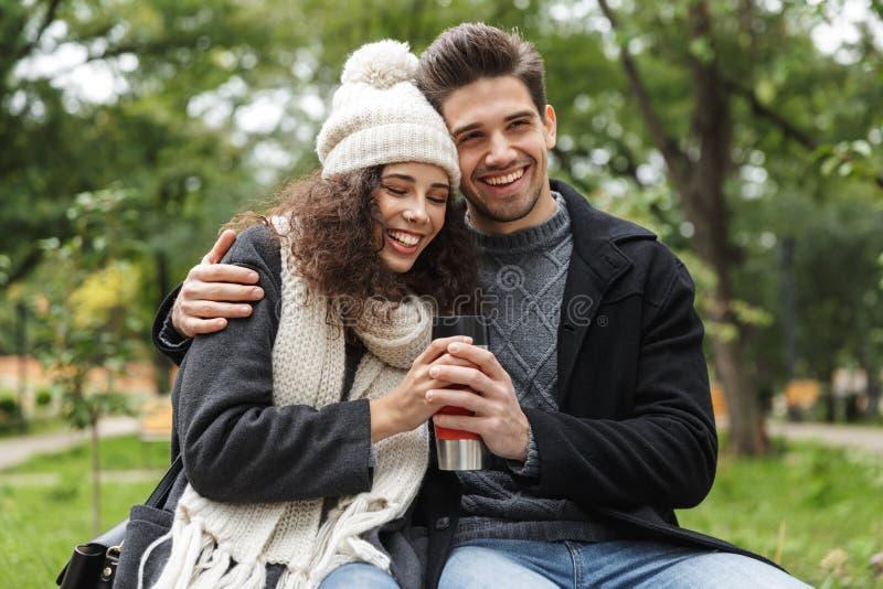 拥抱和拿着热水瓶杯子的满意的人男人和妇女20s画象,当走休息在绿色公园时 库存照片
