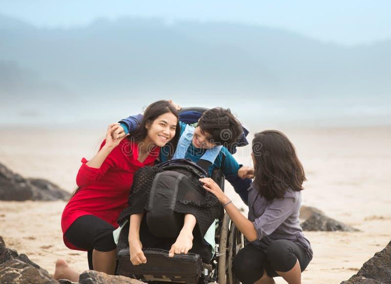 拥抱海滩的轮椅的残疾兄弟姐姐 免版税库存图片