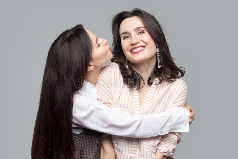 拥抱美丽的长发深色的女孩特写镜头画象和设法亲吻她的最好的朋友或姐妹和另一feelling 免版税库存照片
