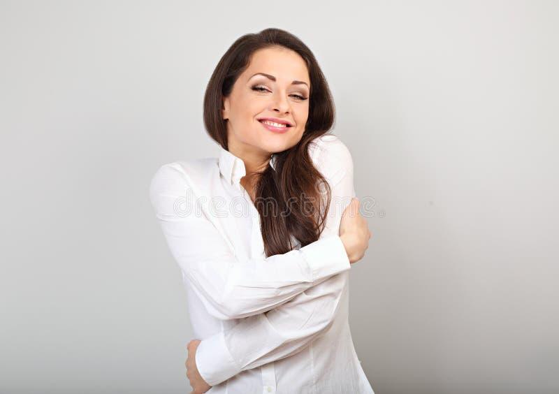 拥抱的愉快的女商人与与闭合的眼睛的自然情感享用的面孔在蓝色背景 概念亲吻妇女的爱人 库存图片
