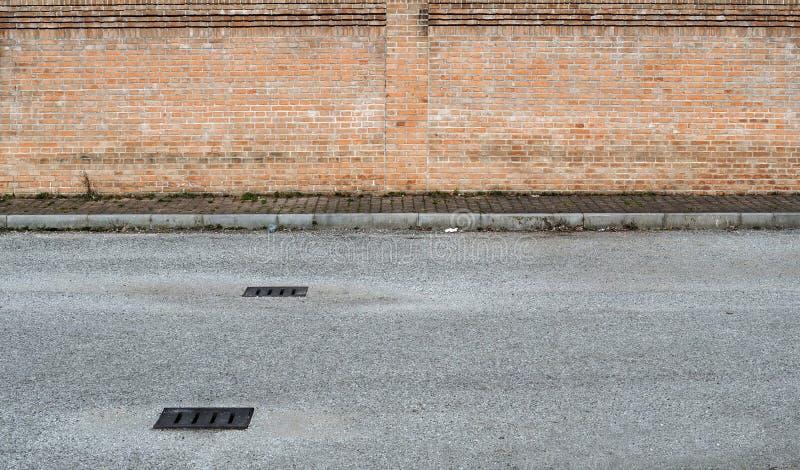 拷贝空间的郊区街道背景 有出入孔的柏油路在有杂草和brickwall的一条边路前面 免版税图库摄影