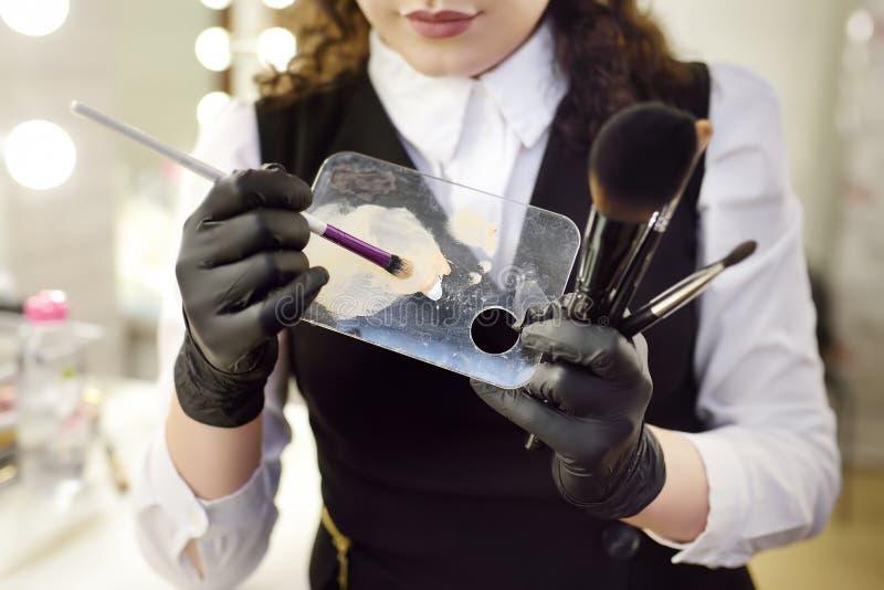 拾起基础的口气的在调色板的化妆师使用特别刷子 面部关心和组成 免版税库存照片