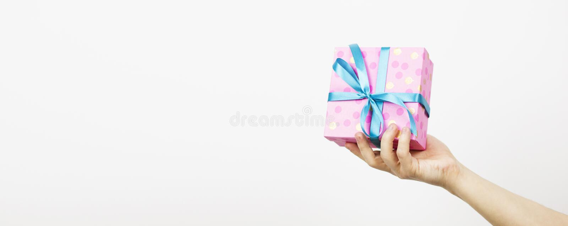 拿着与最高荣誉的女性手一件礼物,在白色背景的一个对象 礼物假日 欢乐的背景 顶视图 免版税图库摄影