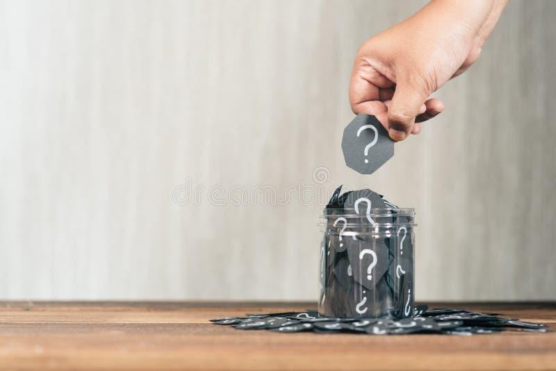 拿着与问号的手黑纸裁减投入或收集它从瓶子 库存照片