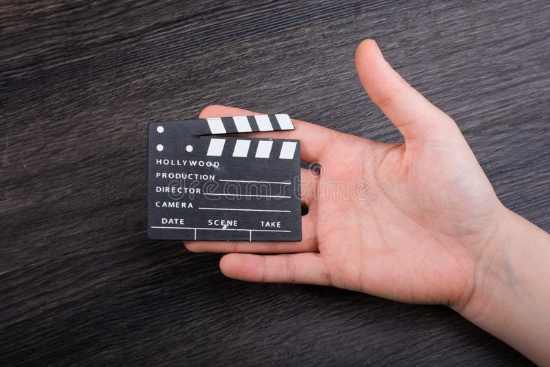拿着一个小的电影拍板的手手中 图库摄影