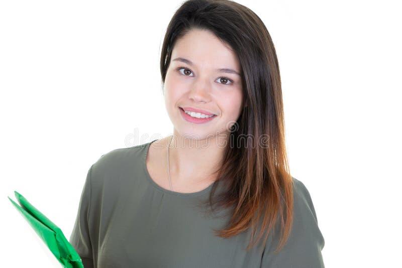 拿着五颜六色的绿色笔记本的逗人喜爱的年轻学生女孩画象  免版税库存照片