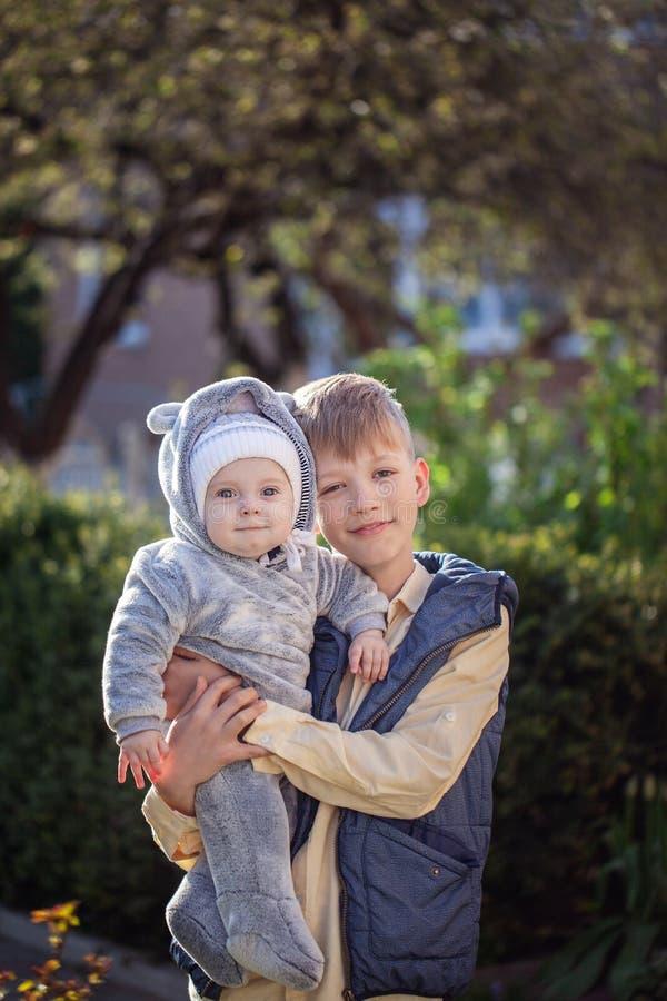 拿着他微笑的男婴的哥哥在一个公园在温暖的春日 免版税库存图片