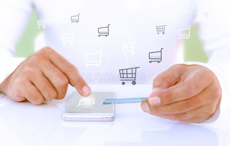 拿着信用卡和使用手机的男性手为网络购物 接触手推车真正按钮的商人 库存例证