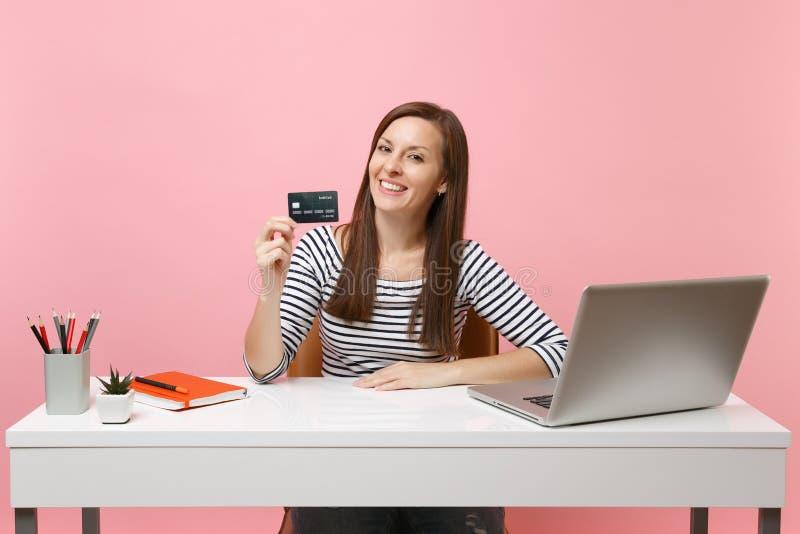 拿着信用卡的年轻成功的妇女工作在有被隔绝的当代个人计算机膝上型计算机的白色书桌坐粉红彩笔 库存照片