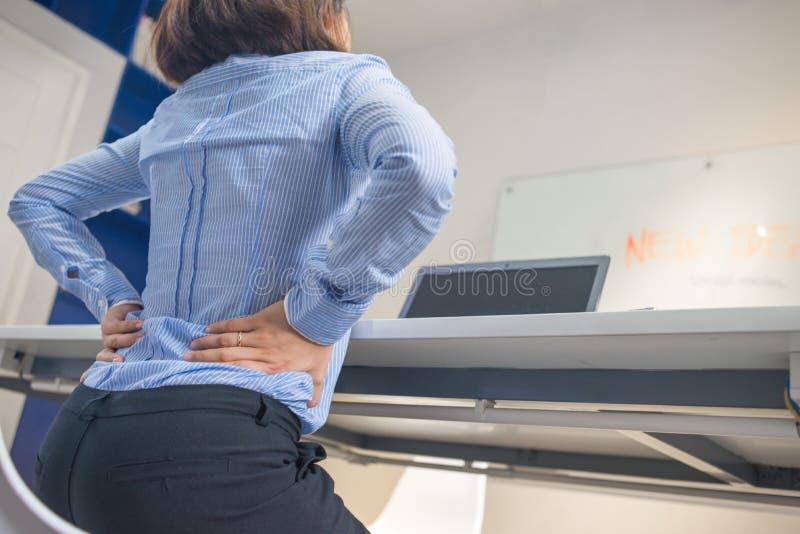 拿着她的后面的女实业家,当研究膝上型计算机时 库存图片