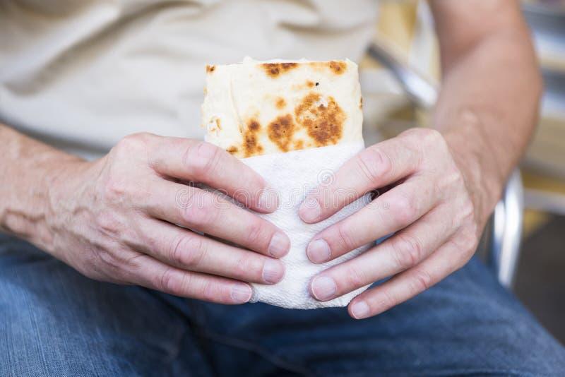 拿着套,面包,piadina的人,反对白色迷离背景 免版税库存照片
